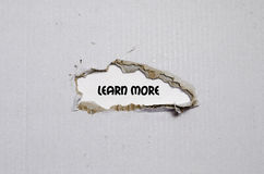The word learn more appearing behind torn paper Stock Photo