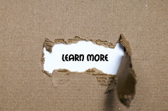 The word learn more appearing behind torn paper Stock Photography