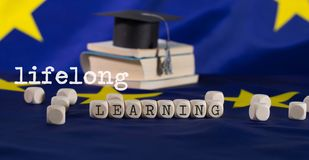 Words LIFELONG  LEARNING  composed of wooden letters. Word  LEARNING  composed of wooden letters.  Black graduate hat on EU flag in the background. Closeup royalty free stock photo