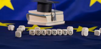 Word  LEARNING  composed of wooden letters. Black graduate hat on EU flag in the background. Closeup royalty free stock photography