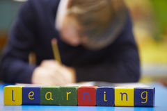 Word Learning Spelt In Wooden Blocks With Pupil Behind Royalty Free Stock Images