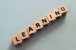 The word learning written in cubes. On grey background Royalty Free Stock Photos