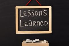 Word lessons learned written on miniature chalkboard. In classroom against black background. Back to school concept. Educational background Stock Photography