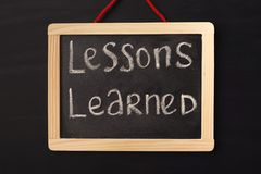 Word lessons learned written on miniature chalkboard. In classroom against black background. Lessons, school, education concept stock photo