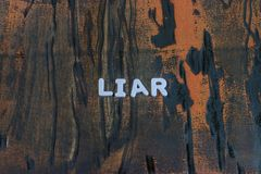 The word liar written in white block letters. On a orange and brown wood surface Stock Photos