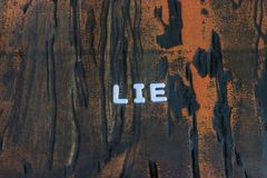 The word lie written in white block letters. On a orange and brown wood surface Royalty Free Stock Photos