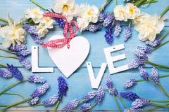 Word liefde en blauwe en witte bloemen op blauwe houten achtergrond Stock Foto