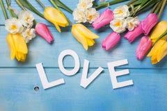 Word liefde en roze, gele en witte bloemen Stock Foto's
