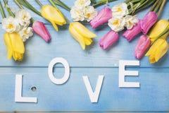 Word liefde en roze, gele en witte bloemen Stock Foto