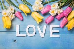 Word liefde en roze, gele en witte bloemen op blauwe houten bac Stock Foto