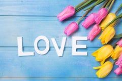Word liefde en roze, gele en witte bloemen op blauwe houten bac Stock Fotografie