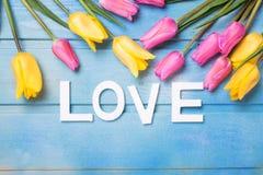 Word liefde en roze, gele en witte bloemen op blauwe houten bac Royalty-vrije Stock Afbeelding