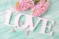 Word liefde en roze hyacintenbloemen op turkooise houten backgr Stock Foto