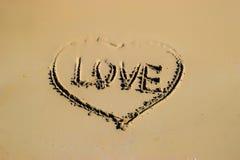 Word liefde en vorm van hart op zand bij het strand door het overzees wordt geschreven, symbool van liefde, de zomertijd die Stock Foto
