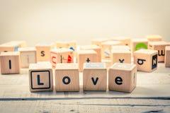 Word ` liefde` houten Kubiek op het hout stock fotografie