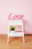 Word liefde in houten, roze gekleurd, met groene installaties wordt gemaakt die Royalty-vrije Stock Afbeelding