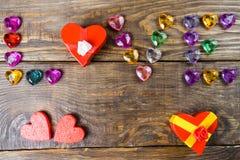 Word liefde maakte jonge harten, twee dozen voor een gift in de vorm van harten en decoratieve harten op houten achtergrond op Royalty-vrije Stock Foto's