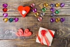 Word liefde maakte jonge harten, twee dozen voor een gift in de vorm van harten en decoratieve harten op houten achtergrond op Stock Foto