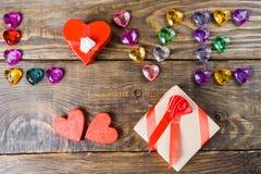 Word liefde maakte jonge harten, twee dozen voor een gift in de vorm van harten en decoratieve harten op houten achtergrond op Royalty-vrije Stock Foto