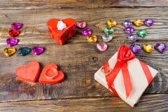 Word liefde maakte jonge harten, twee dozen voor een gift in de vorm van harten en decoratieve harten op houten achtergrond op Stock Afbeelding