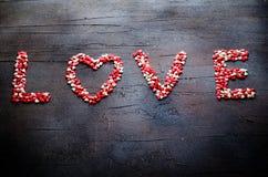 Word Liefde maakte met kleine suikergoedharten, roze, rode, witte kleuren, op donkere achtergrond De dagconcept van de valentijns Stock Afbeeldingen