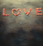 Word Liefde maakte met kleine suikergoedharten, roze, rode, witte kleuren, op donkere achtergrond De dagconcept van de valentijns Royalty-vrije Stock Fotografie