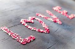 Word Liefde maakte met kleine suikergoedharten, roze, rode, witte kleuren, op donkere achtergrond De dagconcept van de valentijns Stock Foto