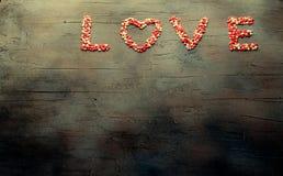 Word Liefde maakte met kleine suikergoedharten, roze, rode, witte kleuren, op donkere achtergrond De dagconcept van de valentijns Royalty-vrije Stock Afbeelding
