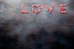 Word Liefde maakte met kleine suikergoedharten, roze, rood, whie kleuren, op donkere achtergrond De dagconcept van de valentijnsk Stock Afbeeldingen