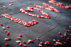 Word Liefde maakte met kleine suikergoedharten, roze, rood, whie kleuren, op donkere achtergrond De dagconcept van de valentijnsk Stock Foto