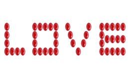 Word liefde met rode geneeskundepillen die wordt gemaakt Stock Foto