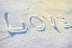 Word LIEFDE op de sneeuw wordt geschreven die Royalty-vrije Stock Afbeeldingen