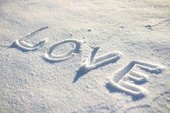 Word LIEFDE op de sneeuw wordt geschreven die Stock Foto's