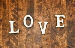 Word LIEFDE op donkere houten achtergrond Stock Afbeeldingen