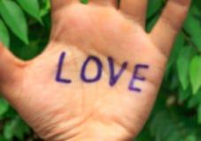 Word liefde op hand, boomachtergrond Royalty-vrije Stock Afbeeldingen