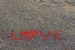 Word LIEFDE op het asfalt, grond wordt geschreven die Rode kleur van krijt Stock Afbeelding