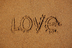Word liefde op het zand wordt geschreven dat Royalty-vrije Stock Afbeelding