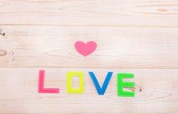 Word liefde op houten achtergrond en hart Rood nam toe Royalty-vrije Stock Afbeelding