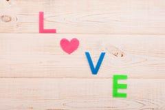 Word liefde op houten achtergrond en hart Rood nam toe Royalty-vrije Stock Afbeeldingen