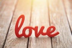Word liefde op houten achtergrond in zonsondergang Stock Foto