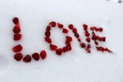 Word Liefde van granaatappelzaden wordt gemaakt op witte sneeuw die royalty-vrije stock foto's