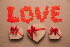 Word Liefde van harten en giftdozen in de vorm van harten Giften voor de dag van Valentine ` s Stock Foto
