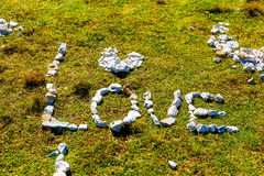 Word liefde van kiezelsteenstenen wordt gemaakt op bergweide die Royalty-vrije Stock Fotografie