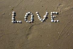 Word liefde van witte verschillende shells in het zand Stock Afbeeldingen