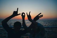 Word liefdesilhouet van twee jongeren die liefdevorm van handen maken bij het strand in de zomertijd van de zonsopganghemel, het  stock foto