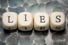 The word lies. Lined with wooden blocks on a metal forged textural background Royalty Free Stock Photography