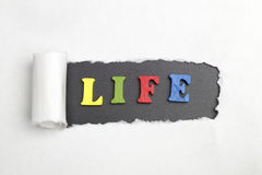 The word life. Broken sheet of paper behind the word life Stock Photos