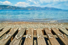 Word lined with small pebbles on wooden sunbed with beautiful la Royalty Free Stock Images