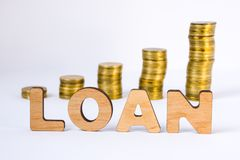 Word loan of three-dimensional letters is in foreground with growth columns of coins on blurred background. Loan concept for start. Ing or development of royalty free stock photos