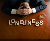 Word Loneliness and devastated man composition Royalty Free Stock Photos